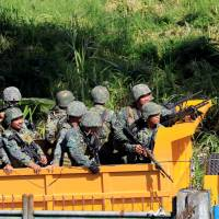 Philippine government troops are seen onboard a truck Tuesday in Amai Pakpak as they continue their assault against insurgents from the Maute group, who have taken over large parts of the city of Marawi, Philippines. | REUTERS