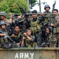 Members of a Philippine police special action force ride in an army truck on their way to the front line in the battle against Islamic State-linked militants in Marawi, on the southern island of Mindanao, on Monday. | AFP-JIJI