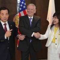 U.S. Defense Secretary James Mattis (center) links hands with South Korean Defense Minister Han Min-koo (left) and defense chief Tomomi Inada ahead of a trilateral meeting at the 2017 International Institute for Strategic Studies Shangri-la Dialogue defense and security forum Saturday in Singapore. | AP