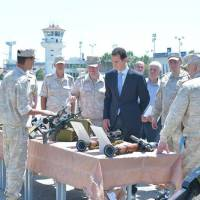 Syrian President Bashar Assad visits a Russian air base at Hmeymim, in western Syria in this handout picture posted on SANA on Tuesday. | SANA / HANDOUT / VIA REUTERS