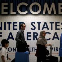 International passengers arrive at Washington Dulles International Airport in Dulles, Virginia, on Monday after the U.S. Supreme Court granted parts of the Trump administration's emergency request to put its travel ban into effect later in the week pending further judicial review. | REUTERS