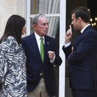 Former New York Mayor Michael Bloomberg talks with French President Emmanuel Macron and Paris Mayor Anne Hidalgo at the Elysee Palace in Paris on Friday. | AP