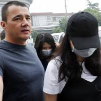 Crown Resorts employee Jiang Ling (rear center) and another employee wearing a face mask, arrive at the Baoshan District People's Court to attend their trial in Shanghai on Monday.   AP