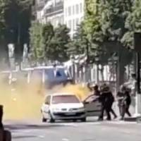 French police engage with a suspect outside a car on the Champs Elysees avenue in Paris Monday in this still image obtained from social media. | EUGENIO MORCILLO / VIA REUTERS