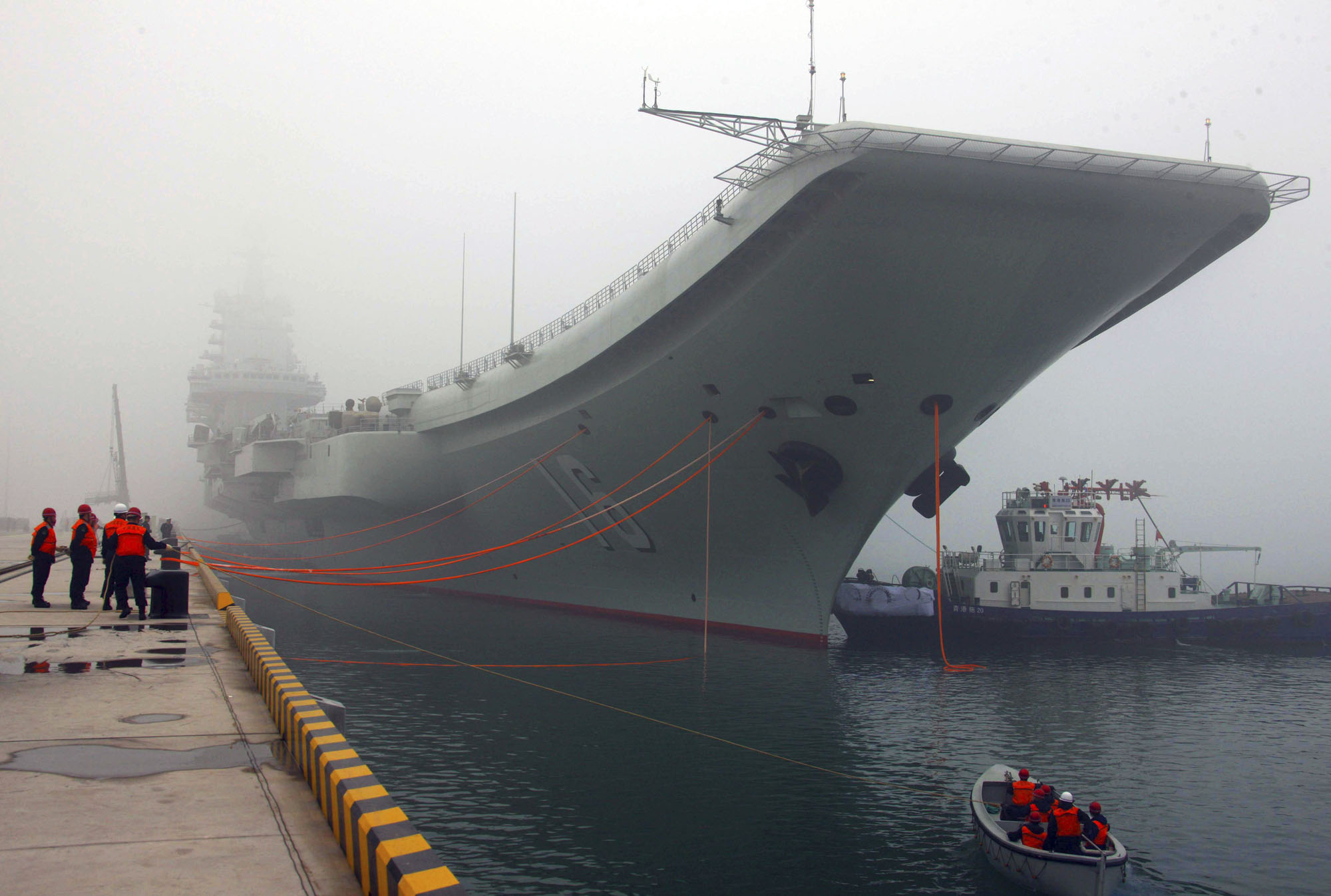 China's first aircraft carrier, the Liaoning, is anchored in the northern port in Qingdao in February 2013. | XINHUA / VIA AP