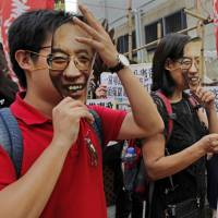 Protesters wear masks of jailed Chinese Nobel laureate Liu Xiaobo during a demonstration outside the Chinese liaison office in Hong Kong on Tuesday. | AP