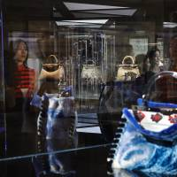 Women look at specially made Italian luxury fashion brand handbags on display at an exhibition in Beijing on Friday. | AP