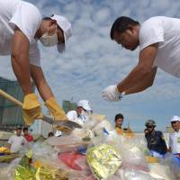 Cambodian officials prepare drugs for a destruction ceremony to mark the U.N.'s International Day against Drug Abuse and Illicit Trafficking in Phnom Penh on Monday.   AFP-JIJI
