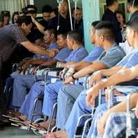 Philippine President Rodrigo Duterte awards a medal and cash to a government soldier who was wounded fighting insurgents from the Maute group, which has taken over large parts of the city of Marawi, during his visit at the military camp hospital in Cagayan De Oro, Philippines, on Sunday. | REUTERS