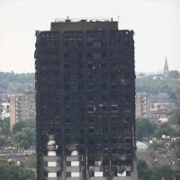 Unburned lower floors with untouched cladding in place are seen with the burnt-out upper floors of the Grenfell Tower block in North Kensington, west London, on Sunday. The presumed death toll from the London tower block inferno jumped to 58 on Saturday as embattled Prime Minister Theresa May, accused of misreading the growing anger over the tragedy, pledged action after meeting survivors desperately seeking answers.   AFP-JIJI