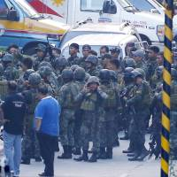 Philippine National Police Special Action Forces prepare to enter the Resorts World Manila complex in suburban Pasay city, southeast of Manila, Friday. A masked gunman stormed the hotel-casino complex early Friday, shooting up a TV screen, torching gambling tables and stuffing a backpack with casino chips before fleeing, authorities said. | AP