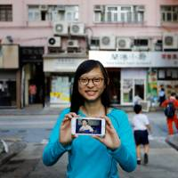 Candy Lau, born five months before Hong Kong's handover to Chinese rule in 1997, poses on June 6 with a 1997 photo of her taken in the building behind her. | REUTERS