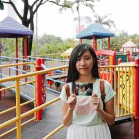Chau Ho-oi, born six months before Hong Kong's handover to Chinese rule in 1997, poses in Kowloon Park on June 3 with a photo of her taken at the same spot in 1999. | REUTERS