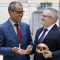 French paleoanthropologist Jean-Jacques Hublin (right) and Abdelouahed Ben-Ncer of Morocco's National Institute of Archaeology and Heritage Sciences pose Tuesday in Paris with the casting of a skull of Homo sapiens discovered in Morocco. | AFP-JIJI