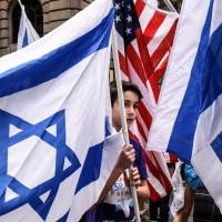 A boy is surrounded by Israeli and American flags during the 'Celebrate Israel' parade along Fifth Ave. in New York City on Sunday. | REUTERS