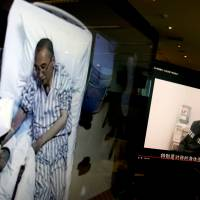 Videos without clear provenance but certainly shot by Chinese authorities show jailed Nobel Peace laureate Liu Xiaobo receiving medical treatment at a hospital (left) and Liu saying wardens take good care of him, on computer screens in Beijing, Thursday. | AP