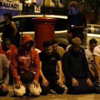 Muslims pray on a sidewalk in the Finsbury Park area of north London after a vehicle plowed into pedestrians Sunday. | AFP-JIJI