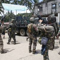 Philippine government troops prepare to head to the front line as fighting with Muslim militants in Marawi city enters its second week in southern Philippines on May 30. The Philippine government said Sunday it would suspend offensives against communist guerrillas to reciprocate a similar plan by the insurgents and allow troops to focus on quelling the bloody siege by Islamic State group-aligned militants that has dragged on for nearly a month in the southern city.   AP