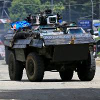 An armored personnel carrier drives along a road in Amai Pakpak on Wednesday as government troops continued their assault against insurgents from the Maute group, who have taken over large parts of the city of Marawi. | REUTERS