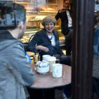 British Prime Minister Theresa May visits a bakery on Tuesday during an election campaign visit to Fleetwood, in the northwestern English county of Lancashire. | BEN STANSALL / POOL / VIA REUTERS