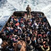 A Libyan coast guardsman stands on a boat during the rescue of 147 illegal immigrants attempting to reach Europe off the coastal town of Zawiyah, 45 km west of Tripoli, on Monday. More than 8,000 migrants have been rescued off Libya during the past 48 hours in difficult weather conditions, Italy's coast guard said on Tuesday.   AFP-JIJI