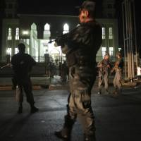 Security forces respond at the site of a suicide attack on a Shiite mosque in Kabul Thursday. A suicide bomber struck outside the mosque killed a leader of Afghanistan's ethnic Hazaras, Hajji Ramazan Hussainzada, and others. | AP