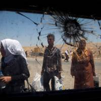 Displaced Iraqi civilians are seen through a shattered glass window of an Iraqi forces armored fighting vehicle in West Mosul, Iraq, Tuesday. | REUTERS