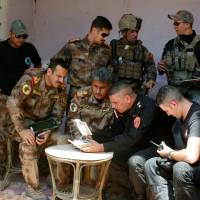 Officers from Iraq's counterterrorism service watch a video transmitted from a drone during a meeting of the Iraqi forces at the front line in the Old City of West Mosul, Iraq, Tuesday. | REUTERS