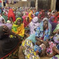 Women mourn following a fatal attack by five female suicide bombers in a village near Maiduguri, Nigeria, on Monday. | AP