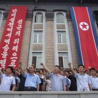 Pyongyang residents take part in a mass rally marking the anniversary of the start of the Korean War on Sunday. | AFP-JIJI