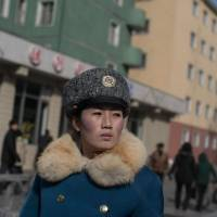 A North Korean traffic security officer stands on duty at an intersection in Pyongyang in February.   AFP-JIJI