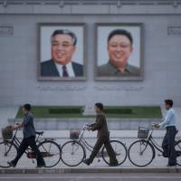 Men push their bicycles past portraits of late North Korean leaders Kim Il Sung and Kim Jong Il in Pyongyang on June 4. | AFP-JIJI