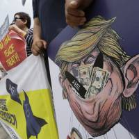 South Korean protesters hold a poster with an illustration of U.S. President Donald Trump during a rally against the deployment of an advanced U.S. missile defense system, near the U.S. Embassy in Seoul on Wednesday. | AP