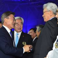South Korean President Moon Jae-in (left) shakes hands with a North Korean delegation led by International Olympic Committee member Chang Ung during the opening ceremony of the World Taekwondo Championships in Muju, South Korea, on Saturday. | AP