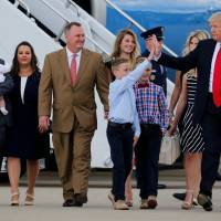 U.S. President Donald Trump, flanked by the families of businesspeople he claims were harmed by Obamacare, high-fives a young boy as he arrives to deliver remarks on the U.S. health care system at Cincinnati Municipal Lunken Airport in Cincinnati, Ohio, Wednesday. | REUTERS