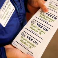 An employee of the advocacy group Basic Rights Oregon hands out stickers during an Oregon Driver and Motor Vehicle department public hearing on the rights of transgender people as the state considers adding a third gender choice to driver's licenses and identification cards, in Portland, Oregon, May 10. | REUTERS