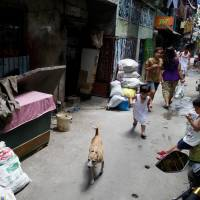 Residents of Manila's Old Balara district pass a house where Philippine police killed seven drug suspects in September 2016 in this photo taken on April 4. | REUTERS