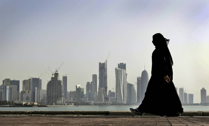 A Qatari woman walks in front of the city skyline in the capital, Doha, in 2010.   AP