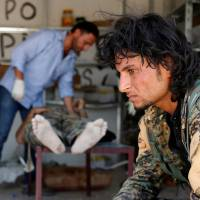 U.S.-backed forces seize last route to complete siege of Raqqa