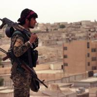April 30 photo provided by the Syria Democratic Forces (SDF) shows a fighter from the SDF carrying weapons as he looks toward the northern town of Tabqa, Syria. U.S.-backed Syrian forces say the battle for control of the Islamic State group's de facto capital Raqqa, in northern Syria, will begin 'within days.'   SYRIAN DEMOCRATIC FORCES /VIA AP, FILE