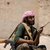 A Syrian Democratic Forces (SDF) fighter carries his weapon and a walkie-talkie in Raqqa's western neighborhood of Jazra, Syria, Sunday.   REUTERS