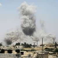 Smoke billows from buildings in the northern Syrian city of Raqqa on Sunday during an offensive by U.S.-backed fighters to retake the Islamic State (IS) group bastion. | AFP-JIJI