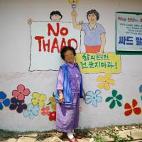 Do Geum-ryeon poses for photographs during an anti-THAAD protest, in Seongju, South Korea, on Wednesday. | REUTERS