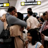 A family embraces each other as members arrive at Washington Dulles International Airport after the U.S. Supreme Court granted parts of the Trump administration's emergency request to put its travel ban into effect later in the week pending further judicial review, in Dulles, Virginia, Monday. | REUTERS