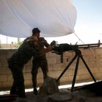 A Kurdish fighter from the People's Protection Units (YPG) fires a heavy machine-gun at Islamic State militants in Raqqa, Syria, Wednesday.   REUTERS