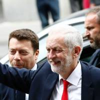 Britain's opposition Labour party Leader Jeremy Corbyn waves as he arrives at Labour Party headquarters in central London on Friday after results came in a snap general election showed a hung parliament.   AFP-JIJI