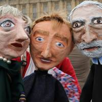 Performers pose with puppet caricatures of Britain's Prime Minister Theresa May, leader of the Liberal Democrat Party Tim Farron and leader of the Labour Party Jeremy Corbyn, in front of the Palace of Westminster in London Thursday. | REUTERS