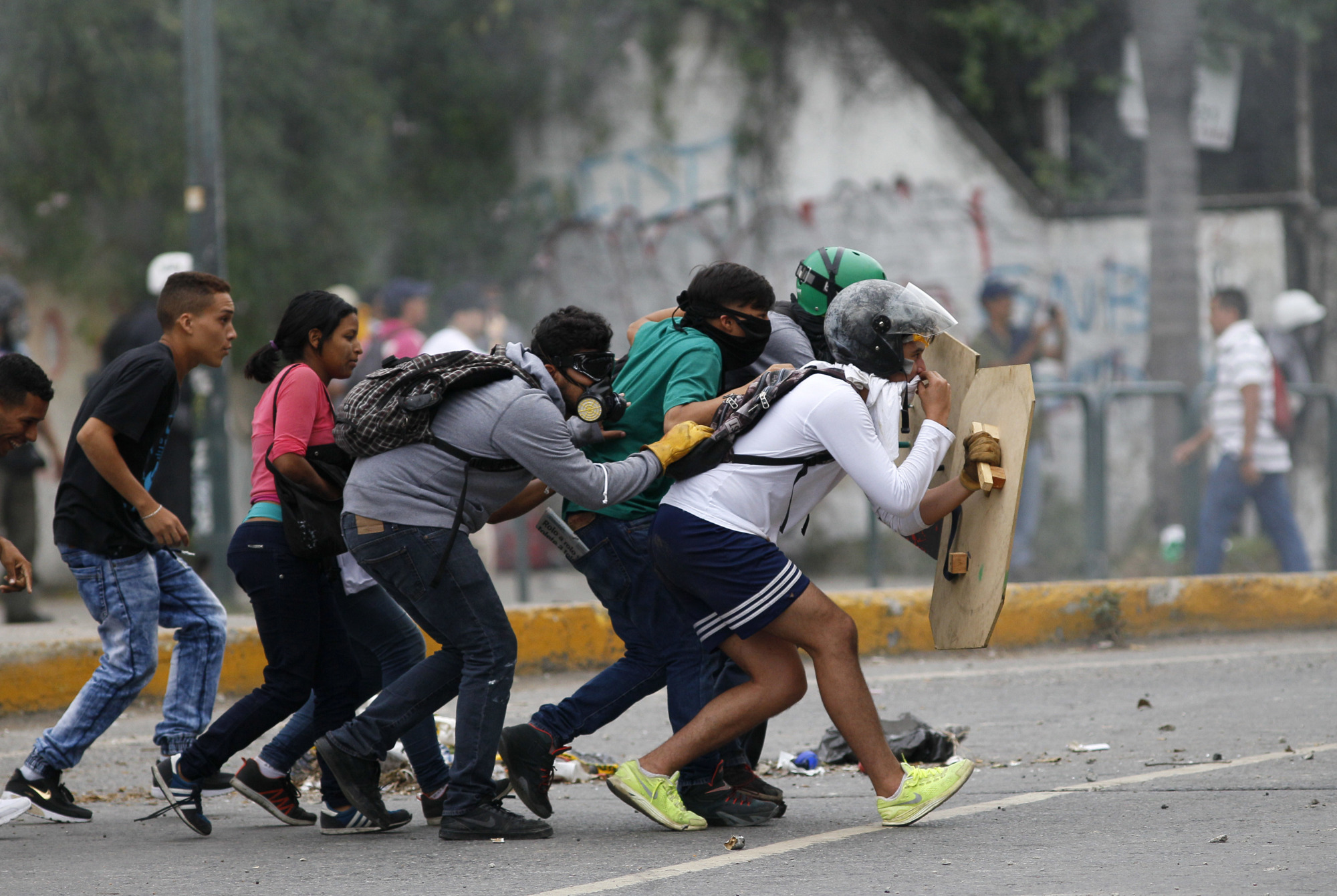 Demonstrators cross the street as they cover themselves with shields during clashes with authorities in Caracas Wednesday. The protest movement has claimed more than 60 lives as it enters its third month. | AP
