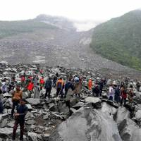 Chinese military police and rescue workers search for survivors at the site of a landslide in the Sichuan village of Xinmo on Saturday. | AFP-JIJI