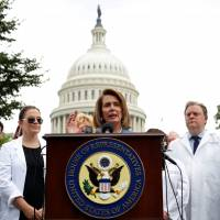 House of Representatives Democratic leader Nancy Pelosi, flanked by healthcare workers, speaks at an event held to protest the proposed Senate Republican healthcare legislation at the U.S. Capitol in Washington, D.C., on Thursday. | REUTERS